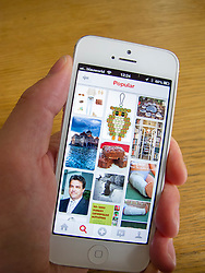 Using Pintrest social media app on  white iPhone 5 smartphone