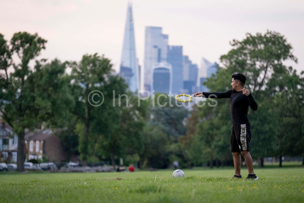 With the Shard and the capitals financial district in the distance, a young man throws a frisbee through the air towards an unseen opponent in Ruskin Park, on 7th June 2021, in south London, England.