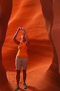 A visitor in the slot canyon known as Secret Canyon on Navajo land, Page, Arizona.  (model released)