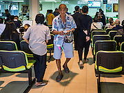 15 DECEMBER 2016 - PRACHINBURI, THAILAND:  A man walks away from the teller windows after picking up his cash disbursements in a government credit union in Prachinburi, Thailand. The Thai government said people who earn 30,000 Baht (about $857 US) or less per year are entitled to a 3,000 Baht cash payment (about $85.7 US) and those who earn 30,000 Baht to 100,000 Baht (about $2,857 US) per year are entitled to a 1,500 Baht (about $42.8 US) cash payment. The plan is meant to help low income people, especially the rural poor. Government banks in rural areas offering the disbursement have been crowded with people seeking their payments this week.     PHOTO BY JACK KURTZ   Social Safety Net
