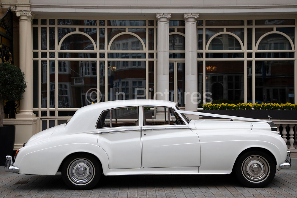 White vintage Rolls Royce wedding car parked outside The Connaught in London, England, United Kingdom.