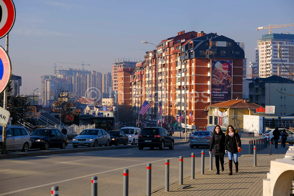 Two women walking past US flags flying on the street George Bush Boulevard Xhorxh Bush on the 13th of December 2018, in Pristina, the capital and largest city of Kosovo, it has a mainly Albanian population along with other smaller communities.  The street was named in honour of the US president to show appreciation for the military support received from the US during the Kosovo war with Yugoslavia.