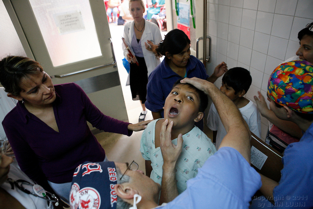 Plastic Surgeon Michael Boyajian, looks at the mouth of Alvaro Aliaga Rodriguez, 10 years old, from Santa Cruz, before Alvaro's lip reconstruction surgery Monday morning, November 12, 2007, at the Hospital Japones in Santa Cruz, Bolivia...Photograph by Erin Lubin