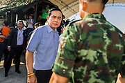 """11 JANUARY 2014 - BANGKOK, THAILAND: General PRAYUTH CHAN-OCHA, Commender in Chief of the Thai Royal Army, walks through a Children's Day fair in Bangkok. The Royal Thai Army hosted a """"Children's Day"""" event at the 2nd Cavalry King's Guard Division base in Bangkok. Children had an opportunity to look at military weapons, climb around on tanks, artillery pieces and helicopters and look at battlefield medical facilities. The Children's Day fair comes amidst political strife and concerns of a possible coup in Thailand. Gen Prayuth has issued mixed signal on a coup at one point saying there wouldn't be one, and later saying he wouldn't talk about a possible coup. Earlier in the week, the Thai army announced that movements of armored vehicles through Bangkok were not in preparation of a coup, but were moving equipment into position for Children's Day.      PHOTO BY JACK KURTZ"""