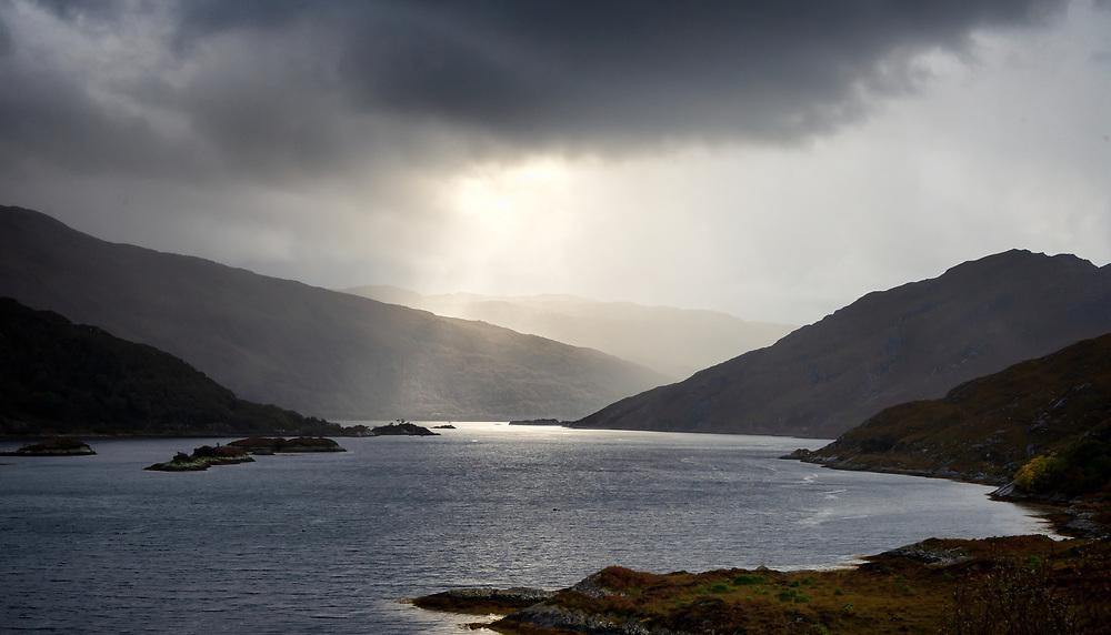 The sun shafts light through complicated cloud banks, rain and mist.