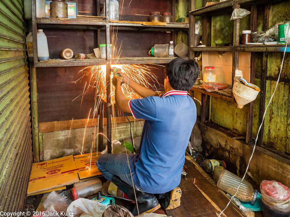 04 JANUARY 2016 - BANGKOK, THAILAND:        A worker takes apart a closed shop in Bang Chak Market after the market closed permanently. The market closed January 4, 2016. The Bang Chak Market serves the community around Sois 91-97 on Sukhumvit Road in the Bangkok suburbs. About half of the market has been torn down. Bangkok city authorities put up notices in late November that the market would be closed by January 1, 2016 and redevelopment would start shortly after that. Market vendors said condominiums are being built on the land.       PHOTO BY JACK KURTZ
