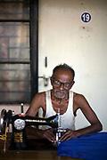 Tanghavil works at his sewing machine outside his room at the Tamaraikulum Elders's Village, Cuddalore, Tamil Nadu, India
