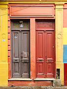 "Orange and gray painted wood double doors in San Telmo barrio, the heart of old Buenos Aires, Argentina, South America. Admire well-preserved old buildings in San Telmo (""Saint Pedro González Telmo""), the oldest barrio (neighborhood) of Buenos Aires, in Argentina, South America."