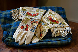 Attributed to Phoebe Anna Traquair HRSA (1852-1936), a pair of gloves embroidered with floral and foliage designs in Native American style