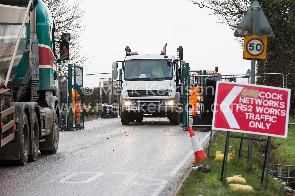 Harefield, UK. 8 February, 2020. Queueing trucks are permitted partial access through a roadblock implemented by HS2 engineers on Harvil Road in the Colne Valley in order to carry out tree felling works for the high-speed rail project. Environmental activists prevented the tree felling by HS2.