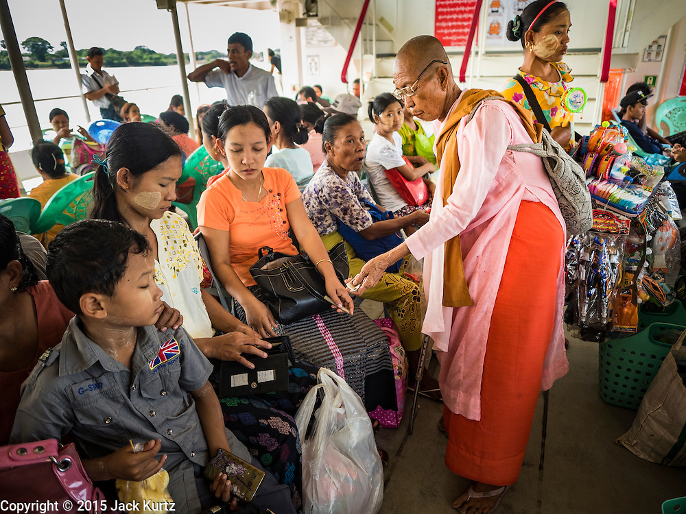 30 OCTOBER 2015 - YANGON, MYANMAR:  A Buddhist nun, also known as a Bhikkhuni, solicits alms (donations) from passengers on the Dala ferry. The ferry to Dala runs continuously through the day between Yangon and Dala. Yangon, Myanmar (Rangoon, Burma). Yangon, with a population of over five million, continues to be the country's largest city and the most important commercial center.          PHOTO BY JACK KURTZ