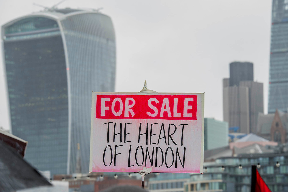 A rally at the end at the foot of City Hall and sandwiched between the City and a new development of luxury flats at One Tower Bridge. People marched from South London and East London to City Hall to demand better homes for Londoners and an end to the housing crisis. Demands included rent controls, affordable and secure homes for all, an end to the Bedroom Tax and welfare caps and the building of new council houses. The event was called by Defend Council Housing and  South London People's Assembly. And the East London route started at Parish Church of St. Leonard, Shoreditch, London, United Kingdom. 31 Jan 2015.