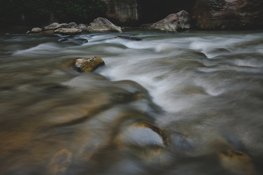 Virgin River water rushing through the rocky riverbed of The Narrows within Zion National Park.