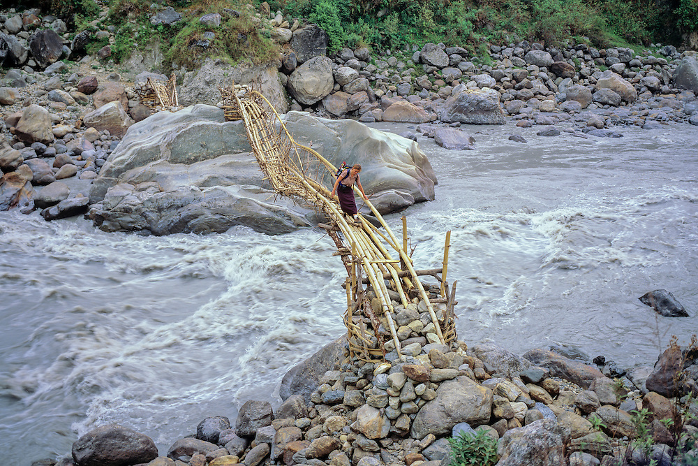 NEPAL,TREKKING,ANNAPURNA RGN Annie crossing bamboo bridge over Marsyangdi R.