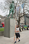 An image of veteran wildlife and environmental broadcaster Sir David Attenborough is held high in Parliament Square next to the statue of Field Marshal Jan Christiaan Smuts, the South African and British Commonwealth statesman, military leader and philosopher, during the week-long protest by climate change activists with Extinction Rebellion's campaign to block road junctions and bridges around the capital, on 23rd April 2019, in London England.