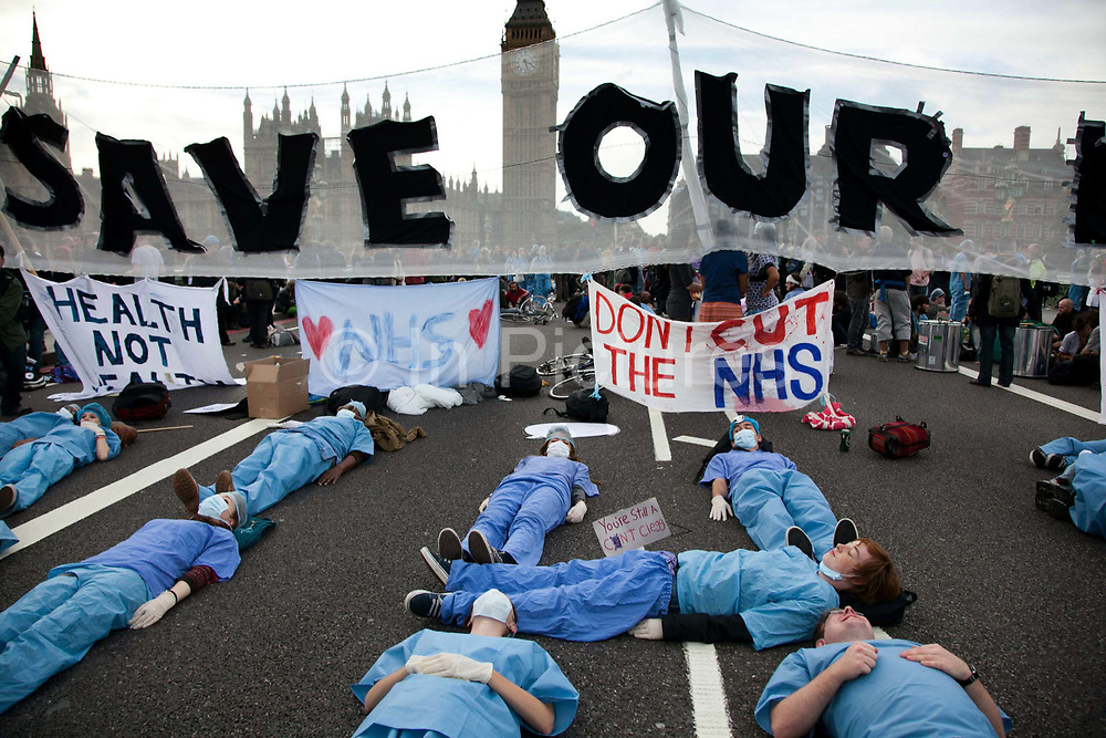 Activists dressed as health workers playing dead.<br /> The Health and Care Bill has been passed by Parliament and is due to go to the House of Lords. In protest against the bill which aim to deconstruct and privatise large parts of the NHS UK Uncut activists together with health workers and trade unionists blocked the Westminster Bridge from 1pm til 5.30pm.