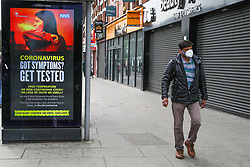 © Licensed to London News Pictures. 22/05/2020. London, UK. A man walks past a 'CORONAVIRUS - GOT SYMPTOMS GET TESTED' digital poster in north London, which is a part of the government's new public information campaign as the lockdown is eased. Photo credit: Dinendra Haria/LNP