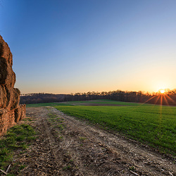 Hay bales in spring in Franklin Township, Pennsylvania. Sunset.