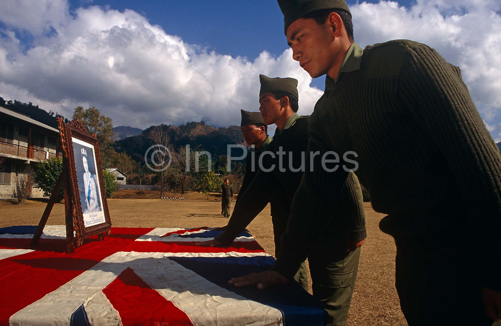 New recruits of the Royal Gurkha Regiment swear allegiance to Her Majesty the Queen's portrait during their passing-out parade at their camp at Pokhara, Nepal. After being recruited into the regiment after a gruelling series of tests to eliminate the weaker and less able candidates, the lucky 160 fly to the UK for basic training. 60,000 boys aged between 17-22 (or 25 for those more educated to become clerks or communications specialists) report to designated recruiting stations in the hills each November, most living from altitudes ranging from 4,000-12,000 feet. After initial selection, 7,000 are accepted for further tests from which 700 are sent down here to Pokhara in the shadow of the Himalayas. Only 160 of the best boys succeed in the journey to the UK. Nepal has been supplying youth for the British army since the Indian Mutiny of 1857