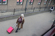 A lady wearing a leopard print coat walks with her pink wheelie case near Elephant & Castle in Southwark, on 27th March 2019, in London, England
