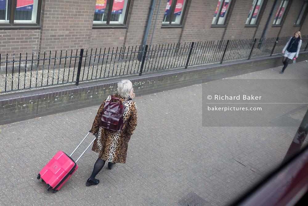 A lady wearing a leopard print coat walks with her pink wheelie case near Elephant & Castle in Southwark, on 27th March 2019, in London, England