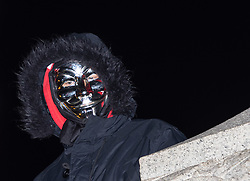 London, November 05 2017. Anti-capitalists gather in Trafalgar Square, London for the annual 'Million Mask March' which happens on November 5th every year, with many of the protesters donning 'V' For Vendetta Guy Fawkes masks. Past marches have turned violent with police horses shot by fireworks and police vehicles burned. PICTURED: A protester in a mask and hoodie stares down from the base of Nelson's column in Trafalgar Square.. © Paul Davey