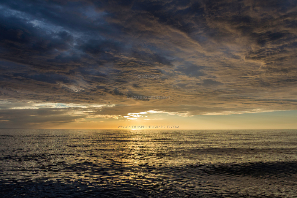 The sun just beginning to set gives off dramatic light to the clouds above Lake Michigan