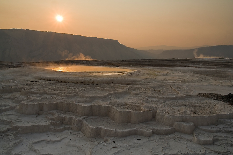The sun rises over the mostly inactive mineral terraces at Mammoth Hot Springs, Yellowstone National Park, Wyoming on September 6, 2006.