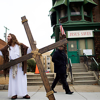 """As a pedestrian looks on, Michael Grant, 28, """"Philly Jesus,"""" hands a supporter his iPhone and headphones after saying goodbye to a friend, while holding a 12 foot cross which he carried 8 miles through North Philadelphia to LOVE Park in Center City as part of a Christmas walk to spread the true message of the holiday in Philadelphia, PA on December 20, 2014.   As many as a half dozen others joined him for numerous miles as he trekked southward down Broad Street.  Some shouted """"Praise Jesus!"""" and """"Thank you for doing this!""""at the sight.  Nearly everyday for the last 8 months, Grant has dressed as Jesus Christ, and walked the streets of Philadelphia to share the Christian gospel by example.  He quickly acquired the nickname of """"Philly Jesus,"""" which he has gone by ever since."""