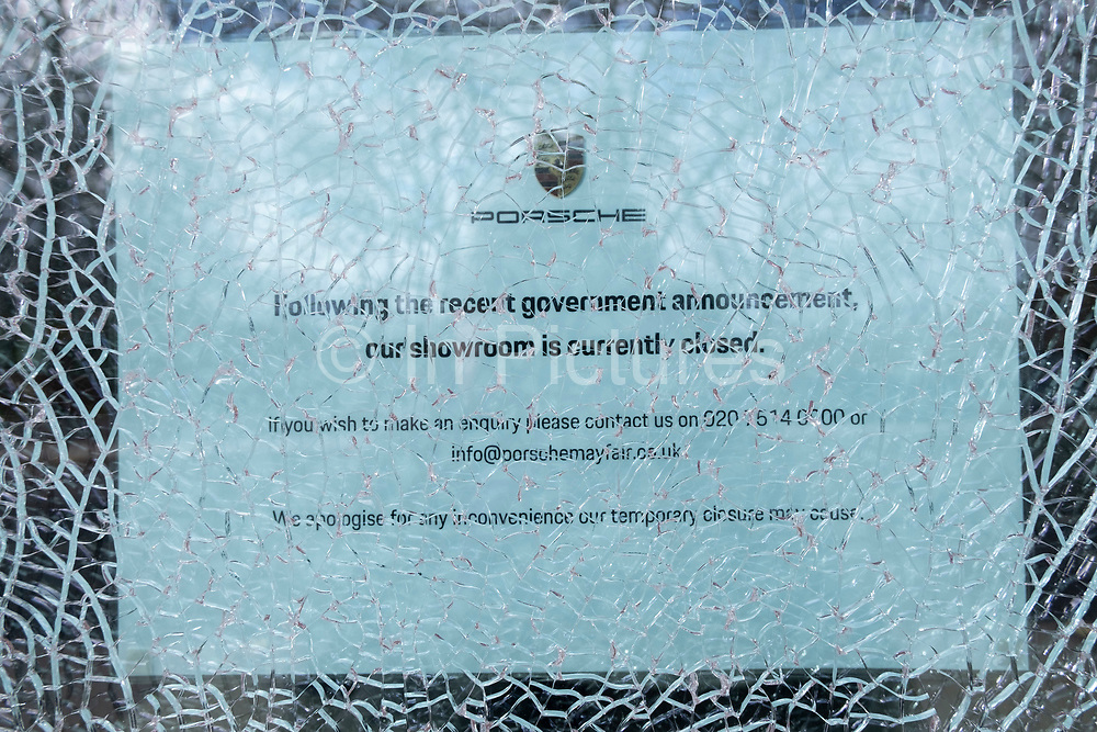 Broken glass over a closed sign in the Porsche showroom in Mayfair as the national coronavirus lockdown three continues on 5th March 2021 in London, United Kingdom. With the roadmap for coming out of the lockdown has been laid out, this nationwide lockdown continues to advise all citizens to follow the message to stay at home, protect the NHS and save lives, and the streets of the capital are quiet and empty of normal numbers of people.