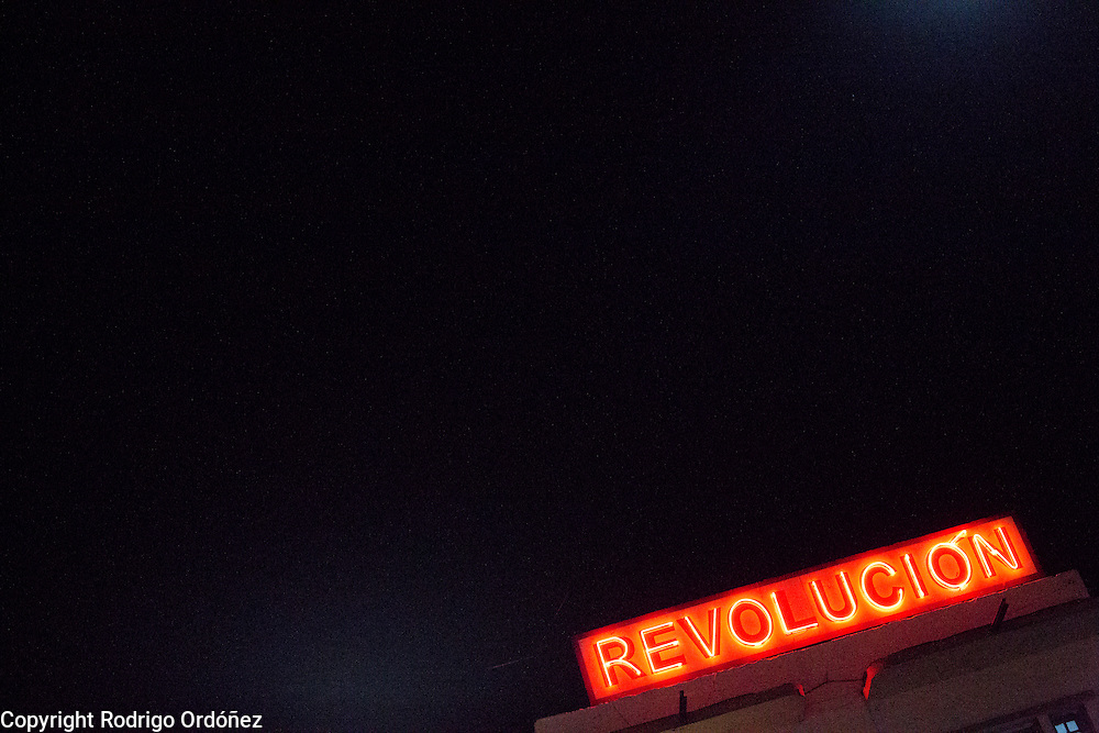 """A neon sign with the word 'Revolución,"""" Spanish for revolution stands on top of a building in the streets of Santiago de Cuba, Cuba, on December 25, 2014."""