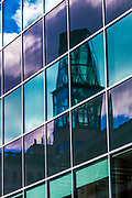 Colorful reflection of the tower of the Museum of civilization Quebec in the windows of a building.