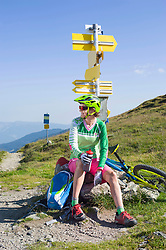 Mountain biker relaxing on hill and drinking water, Zillertal, Tyrol, Austria