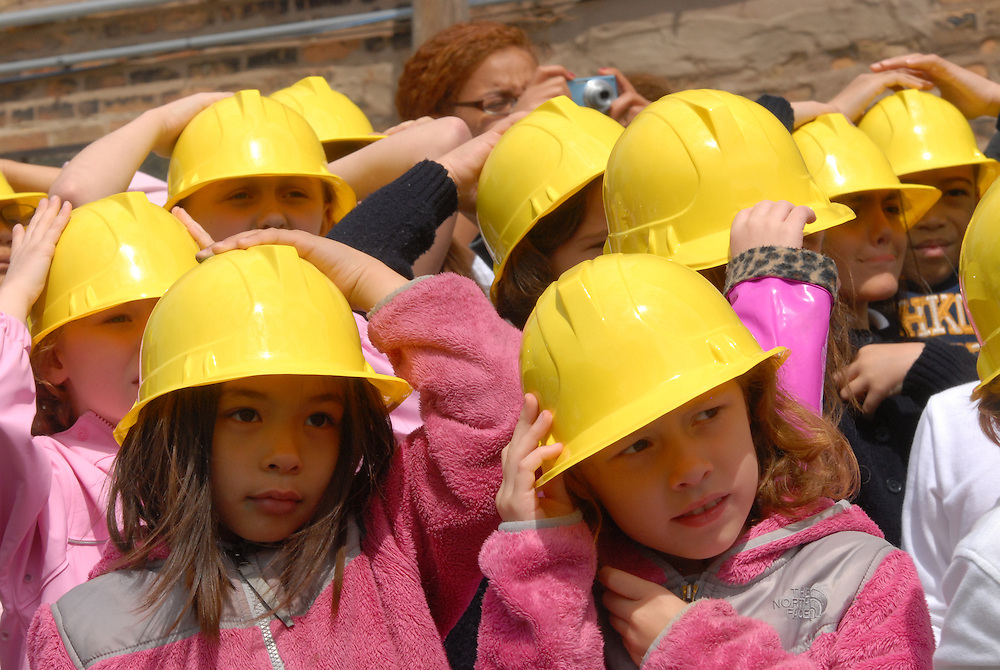 Students at Old St. Mary's Catholic Church in Chicago's South Loop brace their ceremonial plastic hardhats against a threatening breeze during a ground breaking ceremony for their new school attended by Archbishop Francis Cardinal George.