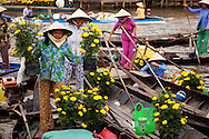 Women offload flowers from boats at the market in Soc Trang. Prior to Tet, the Lunar New Year celebration, the markets are flooded with flowers. The flowers are purchased for homes and kept for good luck. Robert Dodge, a Washington DC photographer and writer, has been working on his Vietnam 40 Years Later project since 2005. The project has taken him throughout Vietnam, including Hanoi, Ho Chi Minh City (Saigon), Nha Trang, Mue Nie, Phan Thiet, the Mekong, Sapa, Ninh Binh and the Perfume Pagoda. His images capture scenes and people from women in conical hats planting rice along the Red River in the north to men and women working in the floating markets on the Mekong River and its tributaries. Robert's project also captures the traditions of ancient Asia in the rural markets, Buddhist Monasteries and the celebrations around Tet, the Lunar New Year. Also to be found are images of the emerging modern Vietnam, such as young people eating and drinking and embracing the fashions and music of the West. His book. Vietnam 40 Years Later, was published March 2014 by Damiani Editore of Italy.