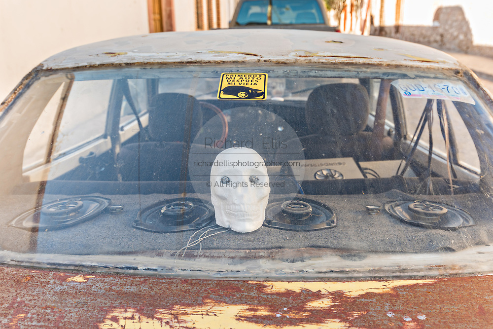 An old car with a skull decoration parked in the ghost town of Mineral de Pozos, Guanajuato, Mexico. The town, once a major silver mining center was abandoned and left to ruin but has slowly comeback to life as a bohemian arts community.