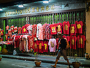 "08 FEBRUARY 2016 - BANGKOK, THAILAND:  A man walks past a sidewalk stand selling Chinese New Year's clothes in Bangkok's Chinatown district during the celebration of the Lunar New Year. Chinese New Year is also called Lunar New Year or Tet (in Vietnamese communities). This year is the ""Year of the Monkey."" Thailand has the largest overseas Chinese population in the world; about 14 percent of Thais are of Chinese ancestry and some Chinese holidays, especially Chinese New Year, are widely celebrated in Thailand.      PHOTO BY JACK KURTZ"