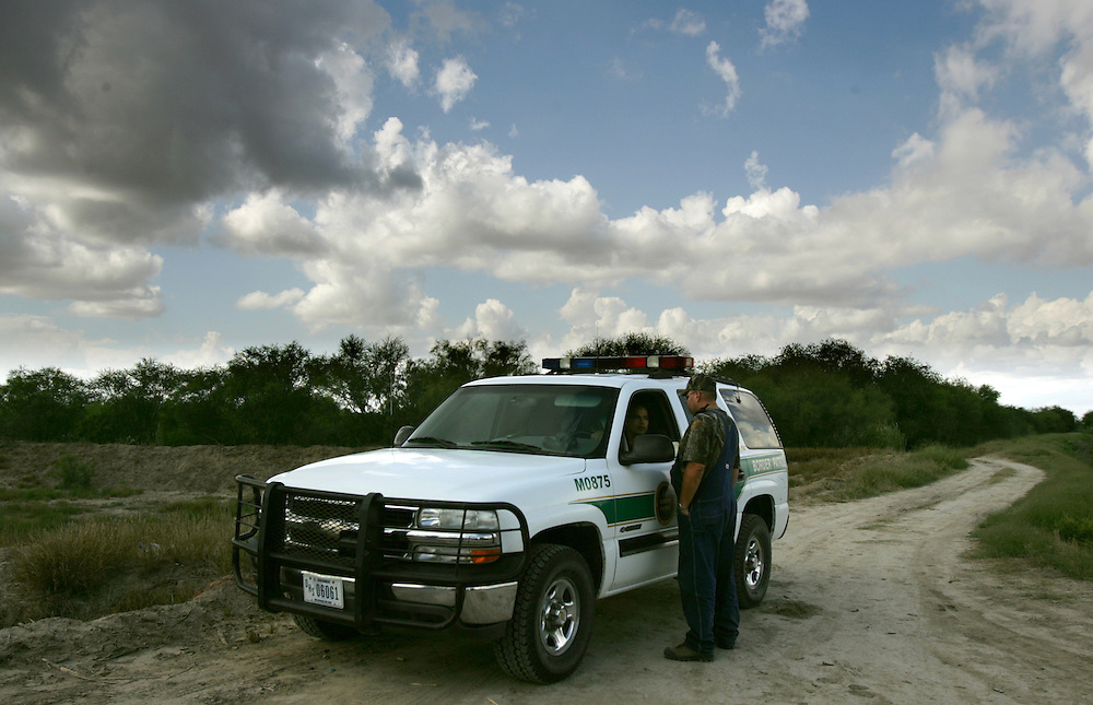 Photo by Alex Jones..Minutemen Civil Defense Corps volunteer David Mitchell talks with a passing Border Patrol agent in a field just East of the Pharr International Bridge on Thursday afternoon.