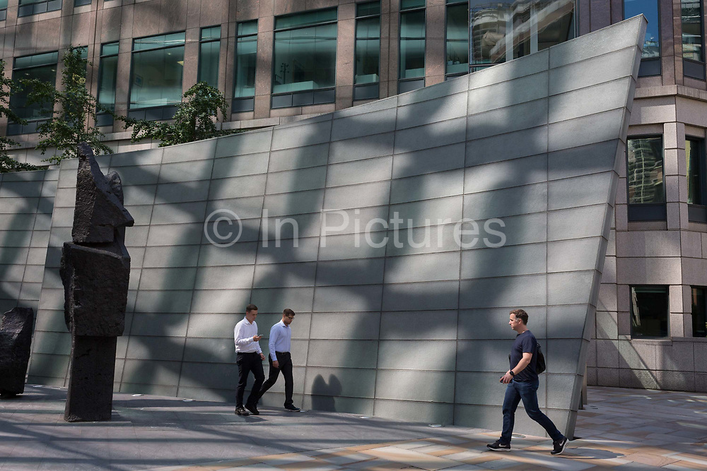 Lunchtime City workers walk through reflected light at Broadgate in the City of London, the capitals financial district - aka the Square Mile, on 8th August, in London, England.