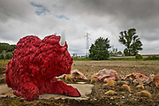 Sculpture of red buffalo on the outskirts of  Carcassonne, France June 2016. The Sculpture is to advertise a resturant chain, Buffalo Grill which can be found all over France. The menu is identical everywhere and offers American-style burgers and steaks.