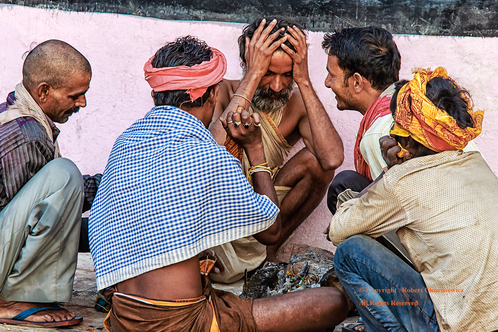 A Hindu devotee sits with his hands on his head with three other men in deep discussion in the early morning at Dashaswamedh Ghat, Varanasi India.