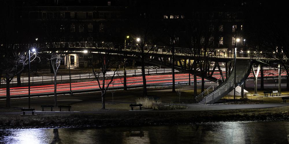 Nighttime traffic passing under the Appleton Bridge along Storrow Drive.