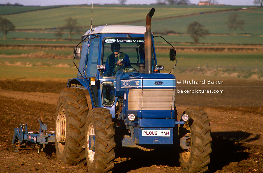 A farmer ploughs his field using a Ford TW-25 tractor in Lincolnshire, England. The large hydraulically-driven machine drives over the land with its plough towed behind over hard-looking ground bought by a local dealer called Sharmans of Grantham, the nearest town. The word Ploughman is on the tractor's front, perhaps a nickname for this local landowner. An escarpment rises in the background towards a farmhouse on its ridge.