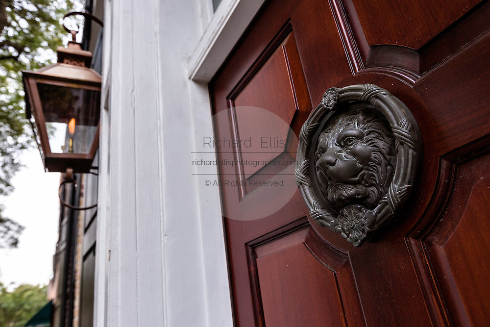 A decorative lion door knocker and gas lamp in the French Quarter in historic Charleston, SC.