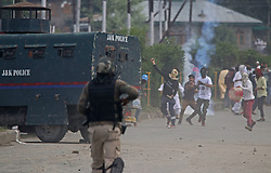 June 16, 2018 - India - Kashmiri youth throws a stone during a clash between protestors and Indian police man  in Srinagar. clashes that broke out after Eid prayers in Srinagar, Indian police and paramilitary forces fired tear smoke shells and pallet guns at hundreds of protestors throwing rocks at them near the main prayer ground Eidgah in Srinagar (Credit Image: © Umer Asif/Pacific Press via ZUMA Wire)