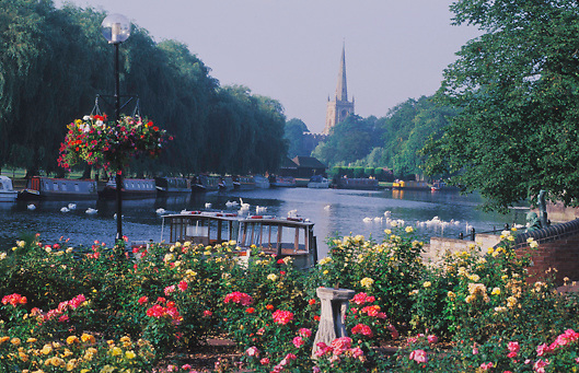View of rose garden, Holy Trinity Church and Barges on River Avon located in Stratford-On-Avon, England.