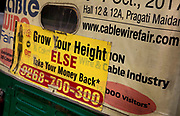 An advertisment to increase your height on the back of a TukTuk on 14th January 2018 on the streets of Delhi, India. A money back guarentee is offered in this display of total optomissm.