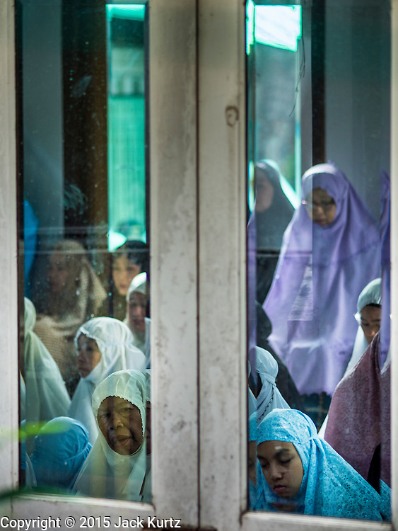 17 JULY 2015 - BANGKOK, THAILAND:     The women's prayer room at Ton Son Mosque in Bangkok is filled for Eid al-Firt services. Eid al-Fitr is also called Feast of Breaking the Fast, the Sugar Feast, Bayram (Bajram), the Sweet Festival or Hari Raya Puasa and the Lesser Eid. It is an important Muslim religious holiday that marks the end of Ramadan, the Islamic holy month of fasting. Muslims are not allowed to fast on Eid. The holiday celebrates the conclusion of the 29 or 30 days of dawn-to-sunset fasting Muslims do during the month of Ramadan. Islam is the second largest religion in Thailand. Government sources say about 5% of Thais are Muslim, many in the Muslim community say the number is closer to 10%.          PHOTO BY JACK KURTZ