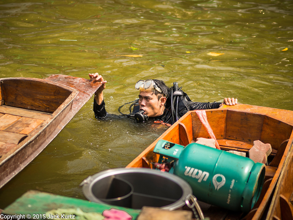 12 FEBRUARY 2015 - BANGKOK, THAILAND: A diver does an inspection of boats in the new floating market on Khlong Phadung Krung Kasem, a 5.5 kilometre long canal dug as a moat around Bangkok in the 1850s. The floating market opened at the north end of the canal near Government House, which is the office of the Prime Minister. The floating market was the idea of Thai Prime Minister General Prayuth Chan-ocha. The market will be open until March 1.    PHOTO BY JACK KURTZ