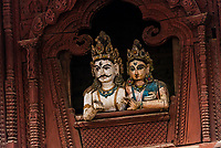 Wood carved statues of Shiva and Parvati sit atop the Shiva Parvati Temple, Durbar Square, Kathmandu, Nepal.